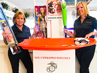 Two Windlass employees holding donations to Toys for Tots