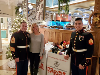 A group of people next to a Toys for Tots donation box.